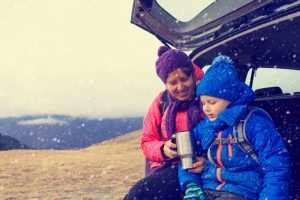 mother and little son travel by car in winter mountains